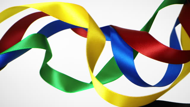 ribbons in olympic colors on white background, for celebration events and party for new year, birthday party, christmas or any holidays, waiving and curling in super slow motion and close up - loopable moving image stock videos & royalty-free footage