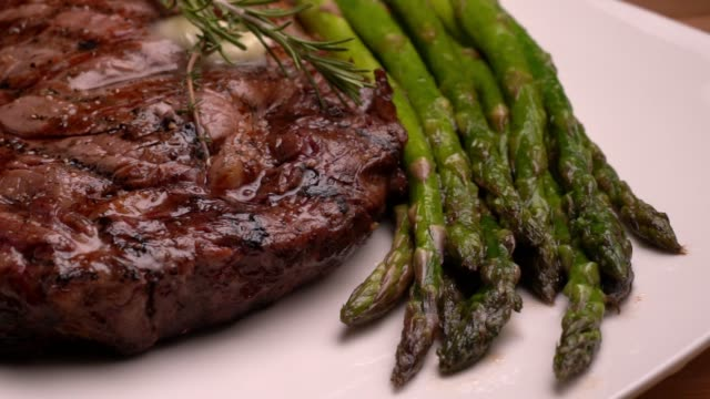 ribeye beef steak on a plate with asparagus ready to eat - steak plate stock videos & royalty-free footage