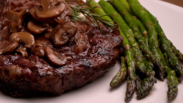 ribeye beef steak on a plate with asparagus ready to eat - plate stock videos & royalty-free footage