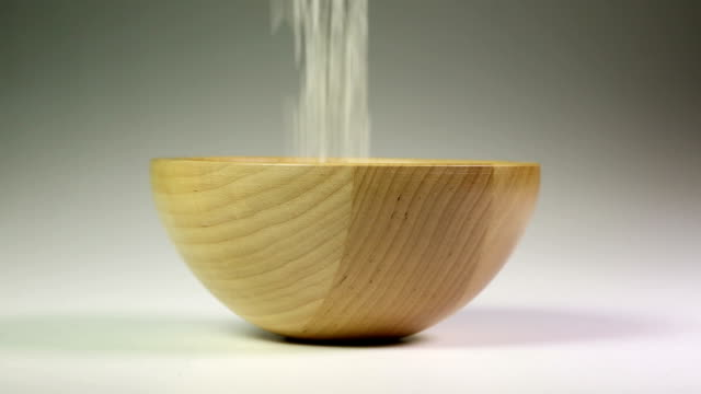 Rice grains fall into a wooden bowl