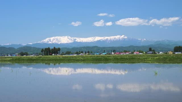 ws aerial rice paddy, town and snowcapped mountains, aizuwakamatsu, fukushima prefecture, japan - mountain range点の映像素材/bロール