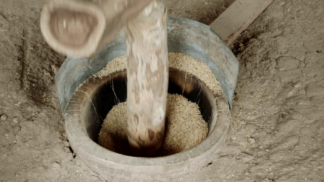 rice pounding with ancient methods - mortar and pestle stock videos and b-roll footage