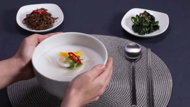 rice-cake soup (or tteokguk, prepared with slices of rice cake, beef, eggs, etc.) and side dishes on the table - korean new year stock videos & royalty-free footage
