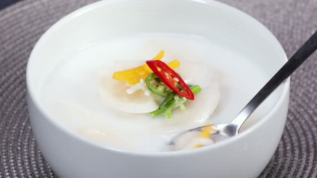 rice-cake soup (or tteokguk, prepared with slices of rice cake, beef, eggs, etc.) and side dishes on the table - capodanno coreano video stock e b–roll