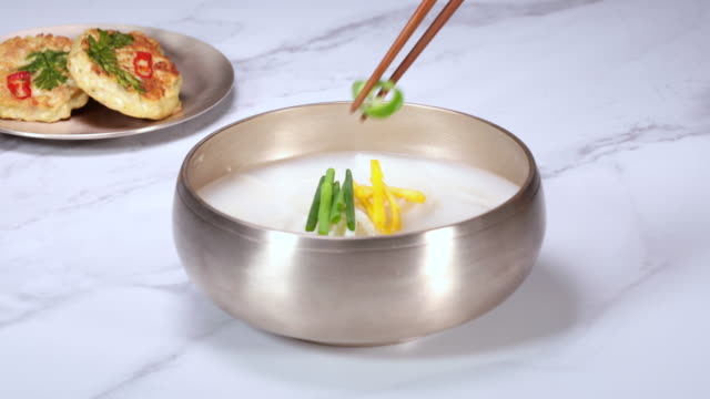 rice-cake soup (or tteokguk, prepared with slices of rice cake, beef, eggs, etc.) with garnish in the bowl - garnish stock videos & royalty-free footage