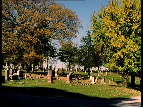 vídeos de stock e filmes b-roll de rich colors of autumn trees in graveyard cut to marble memorial with religious inscription - 1995