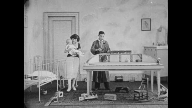 1922 Rich man (Buster Keaton) plays with trains in baby's bedroom