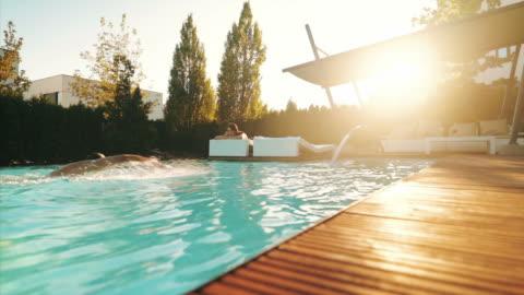 persone ricche che si rilassano nella loro proprietà. - swimming pool video stock e b–roll