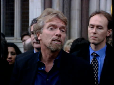 richard branson wins libel case; england: london: the high court: richard branson standing smiling with family and punching the air celebrating... - 文書による名誉棄損点の映像素材/bロール