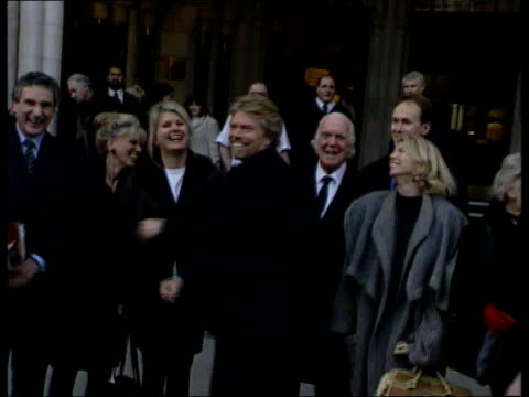 richard branson wins libel case; england: london: the high court: richard branson standing smiling with family and punching air celebrating winning... - 文書による名誉棄損点の映像素材/bロール