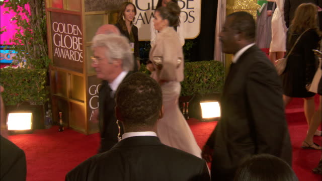 richard gere w/carey lowell walking down the red carpet smiling and waving at the beverly hilton hotel - the beverly hilton hotel stock-videos und b-roll-filmmaterial