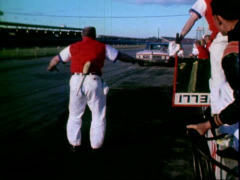 richard petty racing plymouth stock car from pit alley rejoining daytona 500 auto race daytona international speedway daytona florida / pit crew... - circuito di daytona video stock e b–roll