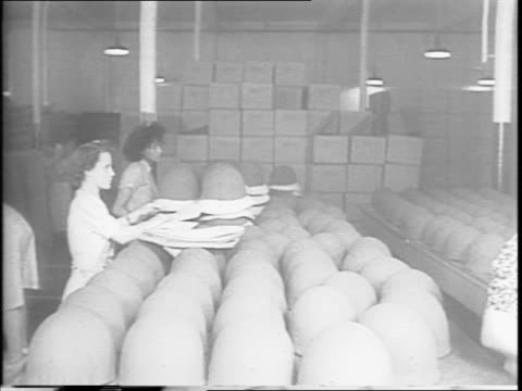 Richardson Molding plant / protective headgear by the thousands roll out of factory manned mostly by women / woman sewing a helmet lining and adding...