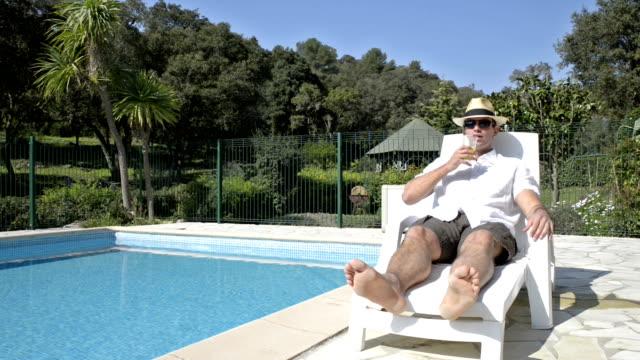 vidéos et rushes de riche homme à la retraite au bord de la piscine - à bord
