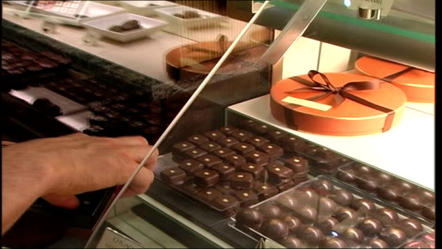 richmond 'chocolatier' wins 'world chocolate award' england london richmonduponthames int william curley arranging chocolate display in his shop... - richmond upon thames stock-videos und b-roll-filmmaterial