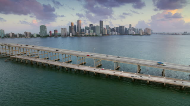 vidéos et rushes de aerial rickenbacker causeway and miami in the background just before sunrise - miami