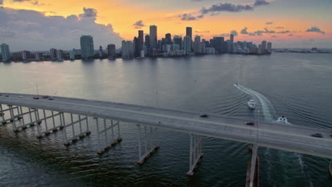 vídeos y material grabado en eventos de stock de aerial rickenbacker causeway con el centro de miami al atardecer - miami