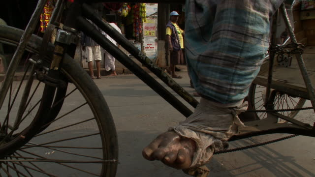 A rickshaw bicycle driver rests his swollen foot on his pedal.