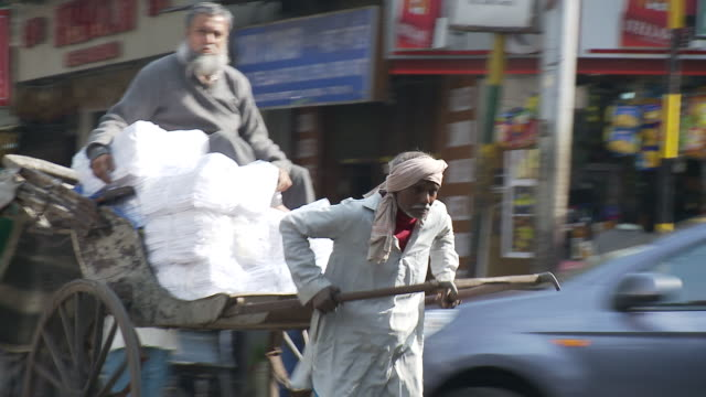 a rickshaw driver dodges traffic as he pulls a passenger and his packages down a street. - rickshaw stock videos and b-roll footage
