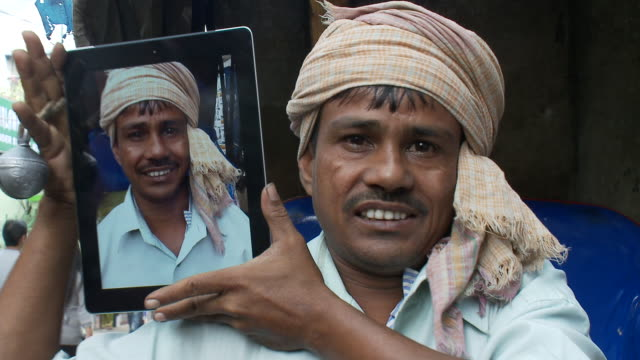 vidéos et rushes de a rickshaw driver holds an ipad with a photo of himself on it. - pousse pousse