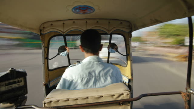 a rickshaw maneuvers through traffic in the city of jaipur, india. - risciò video stock e b–roll