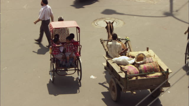 Rickshaw negotiating busy street in New Delhi, India. Available in HD.