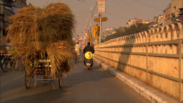 a rickshaw piled high with grasses moves down a street in delhi. - risciò video stock e b–roll