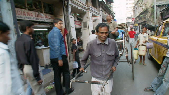 ms slo mo pov rickshaw puller pulling rickshaw with people walking on road / calcutta, west, bengal india - risciò video stock e b–roll
