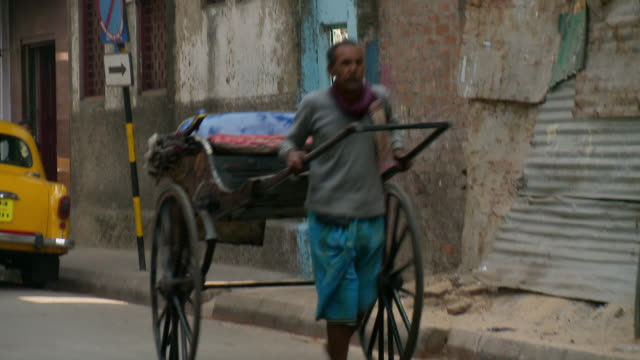 ms ts rickshaw puller with traffic moving on road / calcutta, west, bengal india - risciò video stock e b–roll