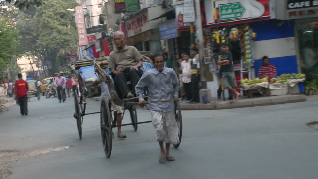 MS TS ZO Rickshaw Pullers pulling rickshaw with people walking on road / Calcutta, West, Bengal India