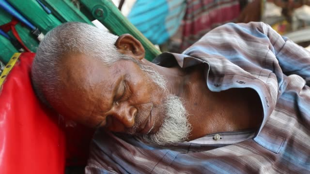 rickshaw pullers sleeping on their tri-wheelers on a hot summer day in dhaka, bangladesh / the city dwellers having a tough time both indoors and... - fahrradtaxi stock-videos und b-roll-filmmaterial