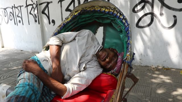 vídeos de stock, filmes e b-roll de rickshaw pullers sleeping on their triwheelers on a hot summer day in dhaka bangladesh / the city dwellers having a tough time both indoors and... - jinriquixá puxado por bicicleta