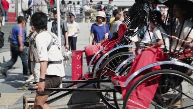 ms a rickshaw runner pulls a jinrikisha through tokyo streets / tokyo, japan - jinrikisha stock videos & royalty-free footage