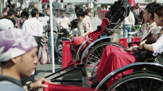WS A rickshaw runner pulls a jinrikisha through Tokyo streets / Tokyo, Japan