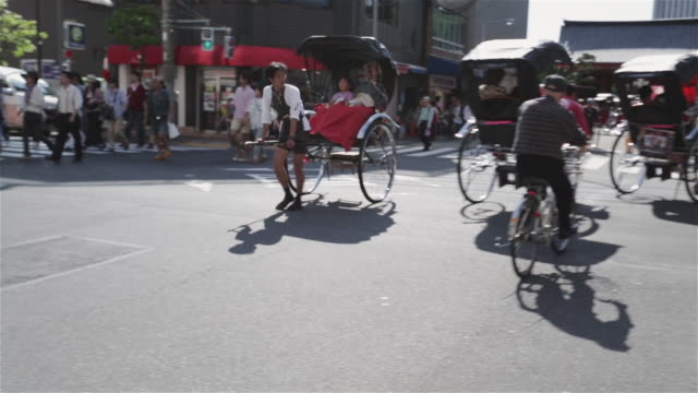 ws a rickshaw runner pulls a jinrikisha through tokyo streets / tokyo, japan - rickshaw stock videos and b-roll footage