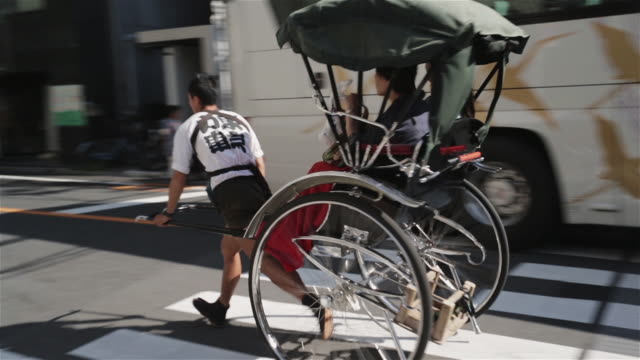 ws a rickshaw runner pulls a jinrikisha through tokyo streets / tokyo, japan - risciò video stock e b–roll