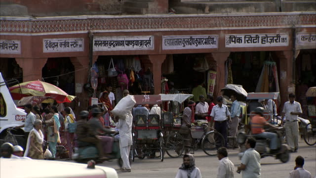 Rickshaws and motorcycles pass street vendors on a crowded street in Jaipur, India. Available in HD