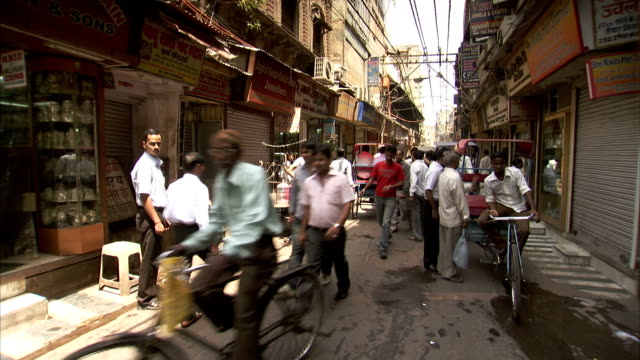 vídeos de stock, filmes e b-roll de rickshaws, cyclists and pedestrians crowd a narrow delhi street. - jinriquixá puxado por bicicleta