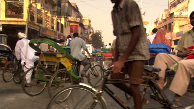 rickshaws, scooters, pedestrians and bicycles fill the streets of delhi. - risciò video stock e b–roll