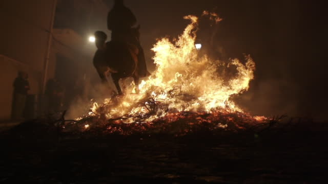 W/S rider and horse crossing a big bonfire, back shot, low angle