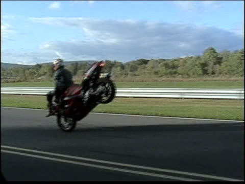 MS, POV, TS, Rider doing front wheelie sitting on motorcycle's handle bars then loosing control, crushing on highway, USA