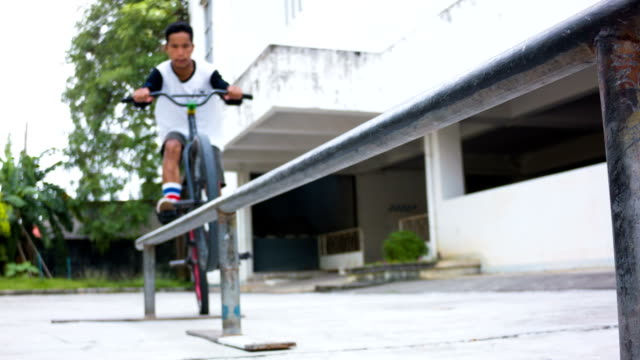 BMX rider grinds on rail