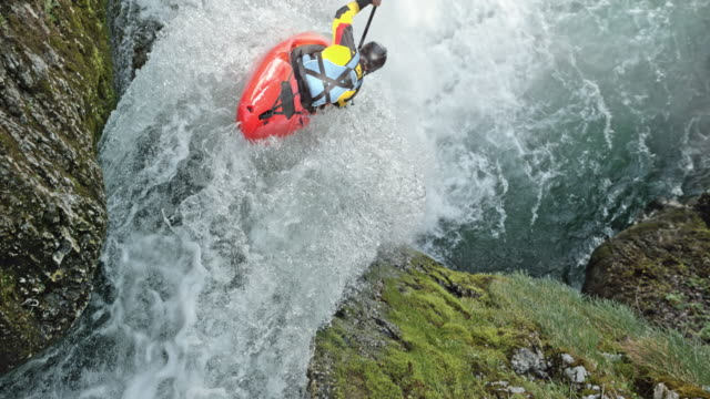 vídeos de stock e filmes b-roll de slo mo rider in a yellow whitewater kayak dropping a waterfall - kayaking