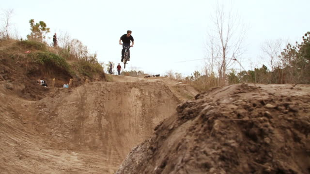 vidéos et rushes de ws pan td bmx rider jumping over dirt mounds, flips in midair and falls off bike / jacksonville, florida, usa - jeunes garçons