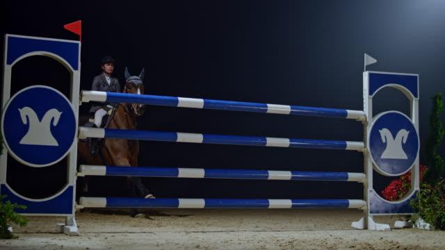 SLO MO Rider on a brown horse jumping a rail at night