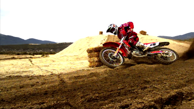 a rider on a motorcycle drifts around a corner and crashes as dirt sprays everywhere during a motocross race. - motocross stock videos & royalty-free footage