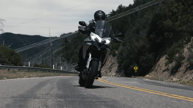 rider on a touring motorcycle on a beautiful mountain road - corner stock videos & royalty-free footage