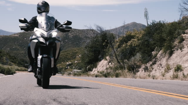 rider on a touring motorcycle on a beautiful mountain road - biker jacket stock videos and b-roll footage