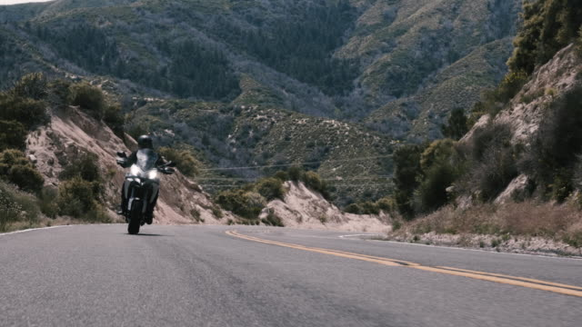 rider on a touring motorcycle on a beautiful mountain road - winding road stock videos & royalty-free footage