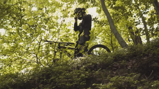 rider on bicycle puts on his protective glasses - mountain bike stock videos and b-roll footage